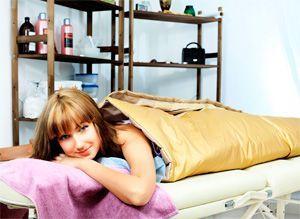 Девушка лежит в спа-салоне на процедуре обертывания