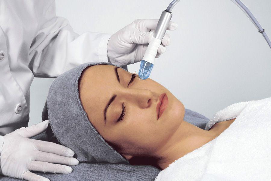 Мастер делает процедуру микродермабразии в салоне красоты