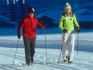Семейная пара зимой занимается скандинавской ходьбой