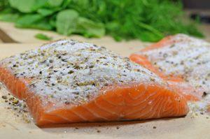 Кусок рыбы семги посыпанный солью и специями