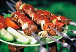 Готовый свиной шашлык с огурцами и помидорами