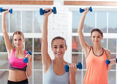 Девушки делают упражнения с гантелями