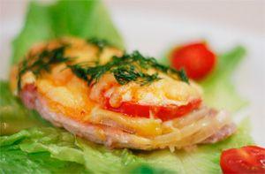 Мясо по-французски из курицы с помидором и сыром на листе салата