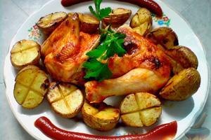 Курица с печеным картофелем и томатным соусом на тарелке