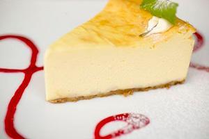 Чизкейк на тарелке украшенной малиновым сиропом