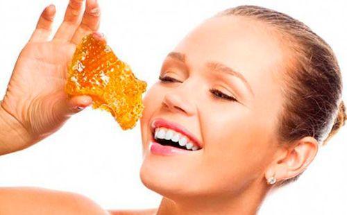 Девушка держит в руках медовые соты