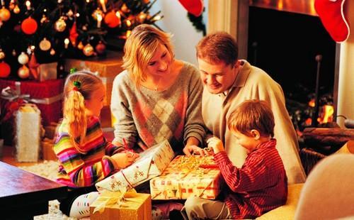 Дети распаковывают подарки возле елки с родителями