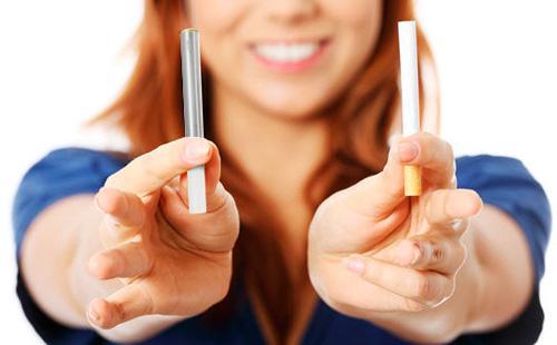 Девушка держит в руках обычную и электронную сигареты