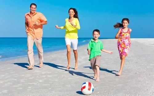 Родители с детьми пинают мяч на пляже