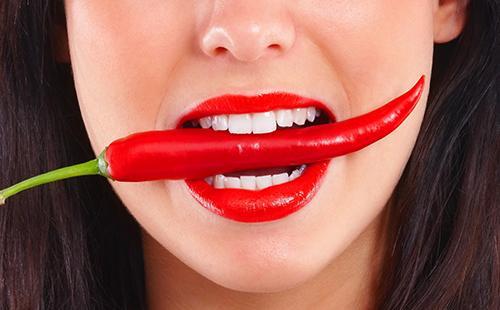 Девушка пытается съесть красный перец