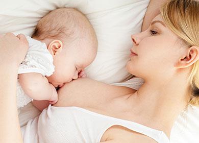 Молодая мама кормит малыша грудью