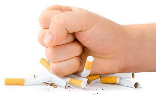 Мужской кулак давит много сигарет