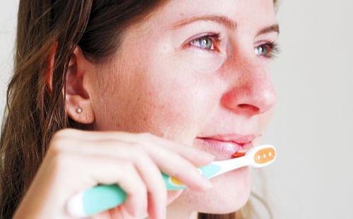 Девушка массирует губы щёточкой