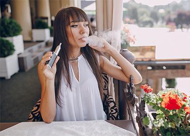 Девушка в кафе курит электронную сигарету