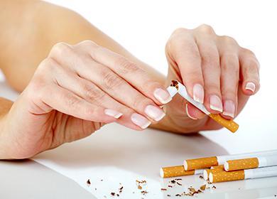 Женские руки ламают сигареты