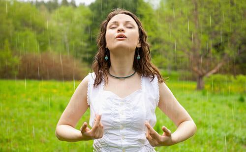 Девушка в белой блузке упивается чистым лесным воздухом