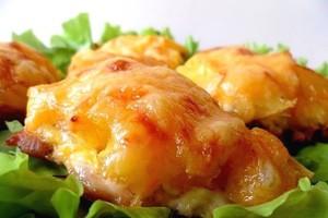 Курица с ананасами и помидорами на листьях салата