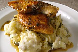 Сочный кусочек цыплёнка возвышается на белой горке из пюре