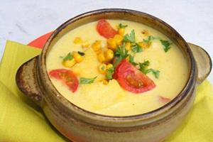 Жёлтая кукуруза, зелень и помидоры в глиняном горшочке