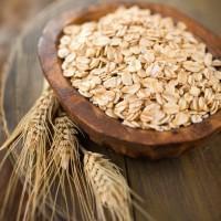 Колоски овса и плющенное зерно в коричневой посуде