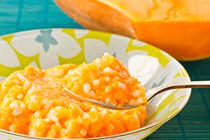 Ярко-оранжевая гарбузовая каша с рисом в пёстрой тарелке