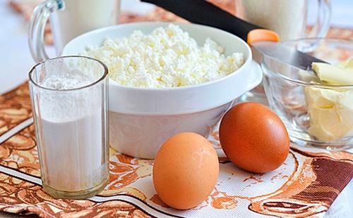 Творог в тарелке, яйца и мука в стакане