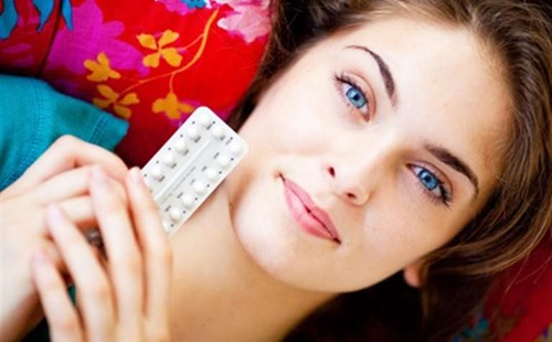 Женщина лежит с пластинкой таблеток в руках