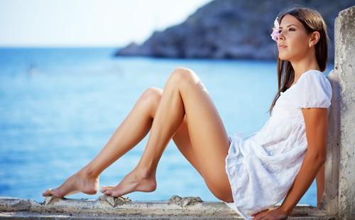 Молодая девушка с гладкими бедрами сидит на берегу моря