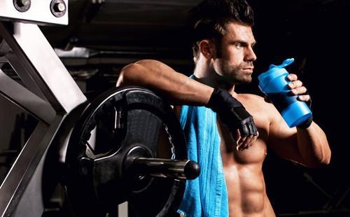 Брутальный мужчина возле штанги в спортзале