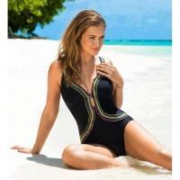 Роскошная девушка в чёрном сидит на песке