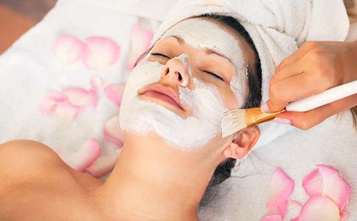 Белая смесь на лице женщины и рассыпанные розовые лепестки