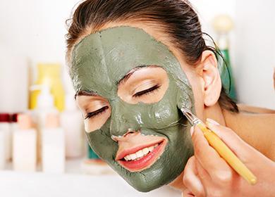 Девушка наносит на лицо маску из глины