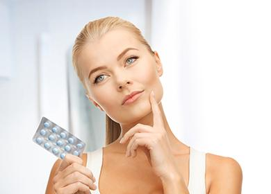 Девушка держит в руке таблетки