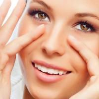 Девушка с улыбкой выполняет простой массаж для глаз