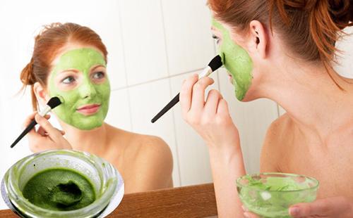 Женщина наносит кисточкой зелёный витаминный состав