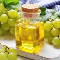 Масло из виноградных косточек среди зелёных кистей ягод