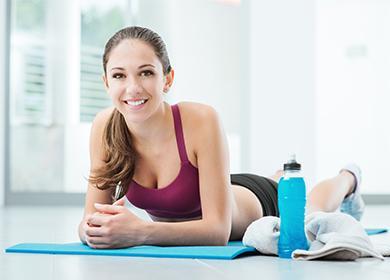 Девушка лежит на тренировочном коврике