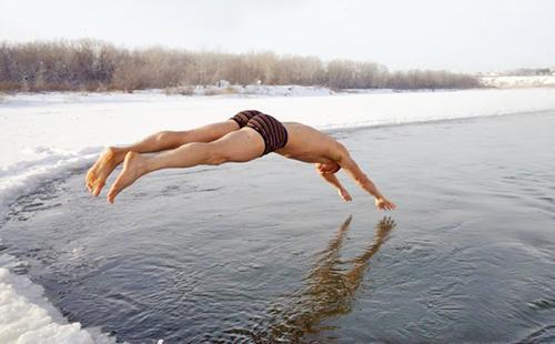 Мужчина эффектно прыгает в зимнюю полынью