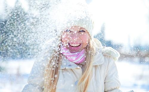 Девушка в белой шапочке радуется снегу