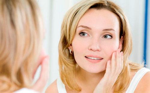 Молодая женщина смотрит в зеркало