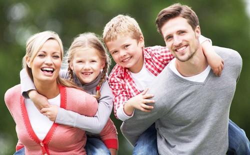 Мама, папа, сын и дочка позируют радостные