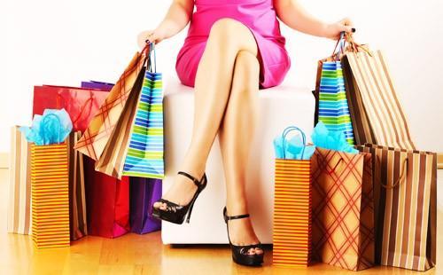 Девушка сидит с кучей пакетов с покупками