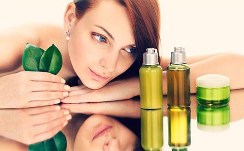 Девушка смотрит на бутылочки с маслом