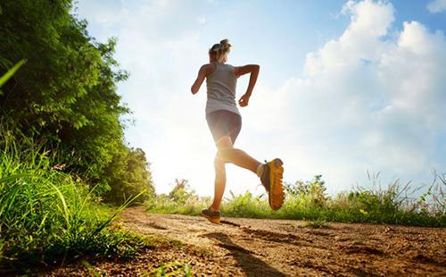 Девушка бежит по тропинке навстречу солнцу