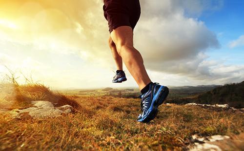 Мужчина в кроссовках бежит к рассвету