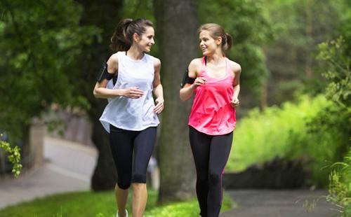 Две девушки смеются и болтают на бегу