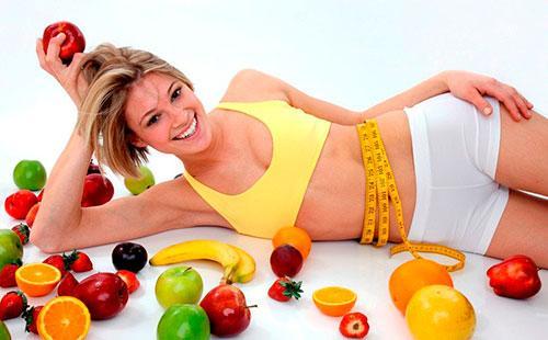 Девушка лежит возле овощей и фруктов
