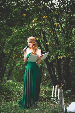 Екатерина в длинном зелёном платье говорит в микрофон
