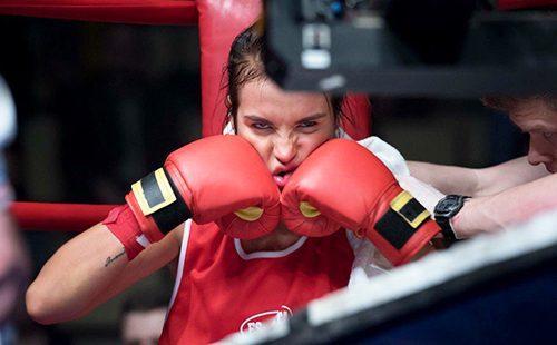 Боксёрша сидит в углу ринга