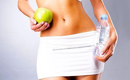 Яблоко и бутылка с водой в руках